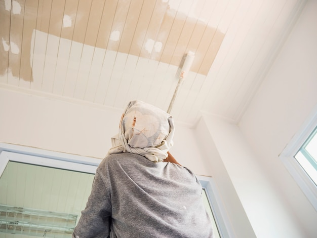 Partial focus photo of a man is painting ceiling using roller brush