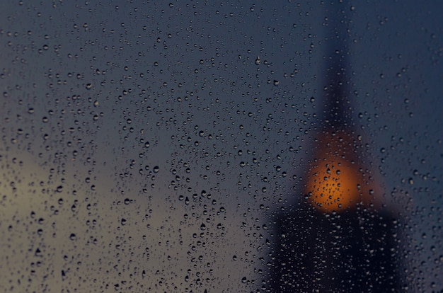Partial focus of rain drop on glass window in monsoon season with blurred  pagoda of temple  background.