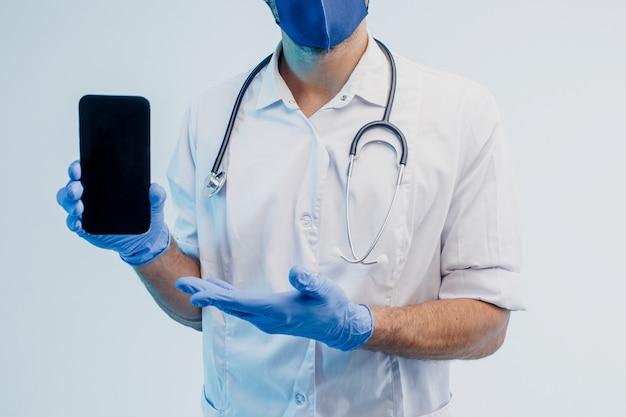Частичное изображение европейского мужского врача, показывающего мобильный телефон. человек со стетоскопом в белом халате, защитной маске и латексных перчатках. изолированные на сером фоне с бирюзовым светом. студийная съемка