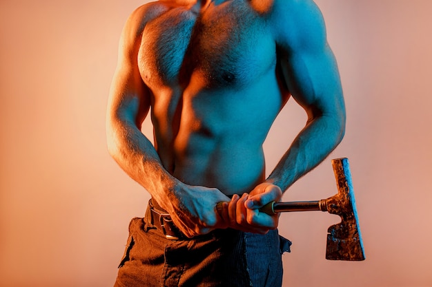 Частичное изображение человека со старым железным топором в руках. сексуальный мускулистый парень с обнаженным спортивным торсом. изолированные на бежевом фоне с синим светом. студийная съемка. копировать пространство