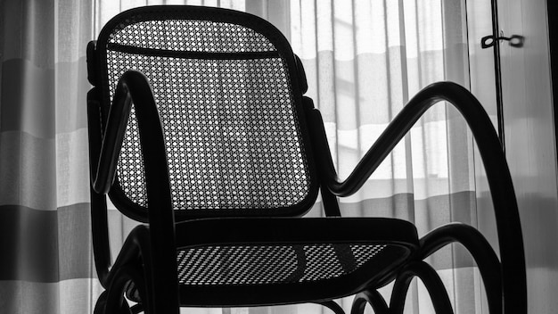 Partial photograph of a rocking chair in black and white style.