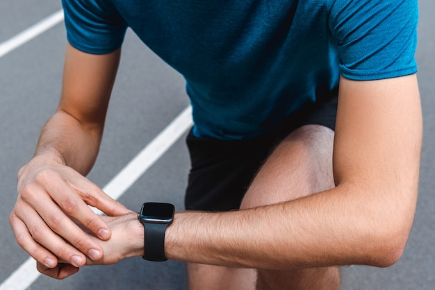 Partial view of athletic young sportsman showing smartwatch with blank screen on running track
