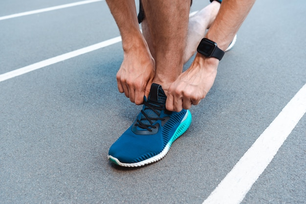 Partial view of athletic young sportsman in smartwatch tying shoelaces on running track