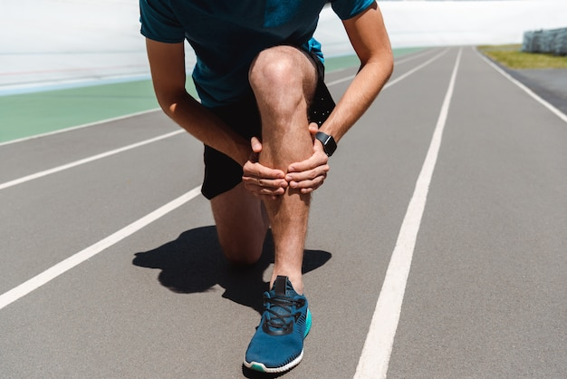 Partial view of athletic young sportsman touching painful leg on running track
