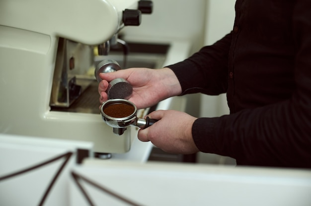 Partial view of barista in black shirt holding portafilter with ground coffee and tamper
