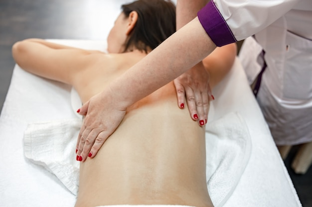 Partial view of masseur massaging back of young woman lying on massage table.
