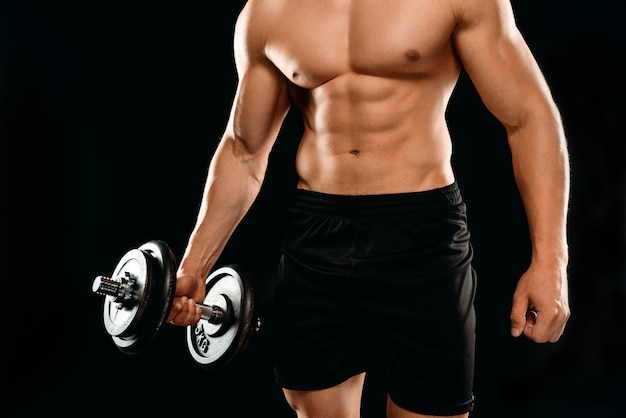 黒に分離されたダンベル運動筋肉の胴とセクシーなボディービルダーの部分的なビュー