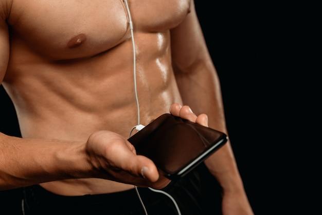 黒に分離されたスマートフォンでイヤホンで音楽を聴く筋肉の胴とセクシーなボディービルダーの部分的なビュー