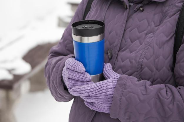 겨울 날에 뜨거운 음료와 thermocup를 들고 여자의 부분보기.