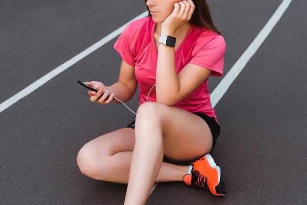 Частичный вид женщины в smartwatch с помощью смартфона и прослушивания музыки на беговой дорожке