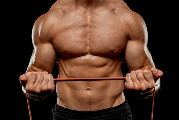 Partial view of sexy bodybuilder with muscular torso exercising with elastic band isolated on black