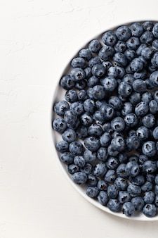 Partial view of a white plate filled with blueberries on white