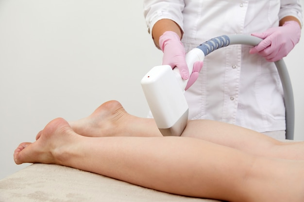 Partial view of woman receiving laser hair removal epilation on leg in a salon