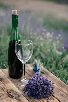 Partially blurred bottle of red wine, glass and bunch of lavender on wooden board against background of bushes of flowers. vertical
