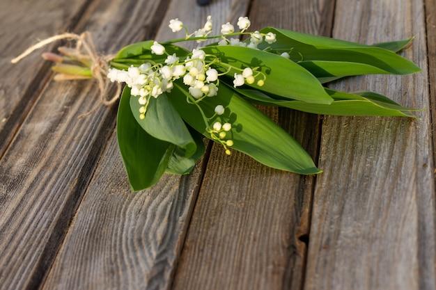 素朴な古い木の表面に部分的にぼやけた花。ボード上の谷のユリの花束。スペースをコピーします。
