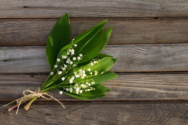 木の表面に部分的にぼやけた花。ボード上の谷のユリの花束。上面図。スペースをコピーします。