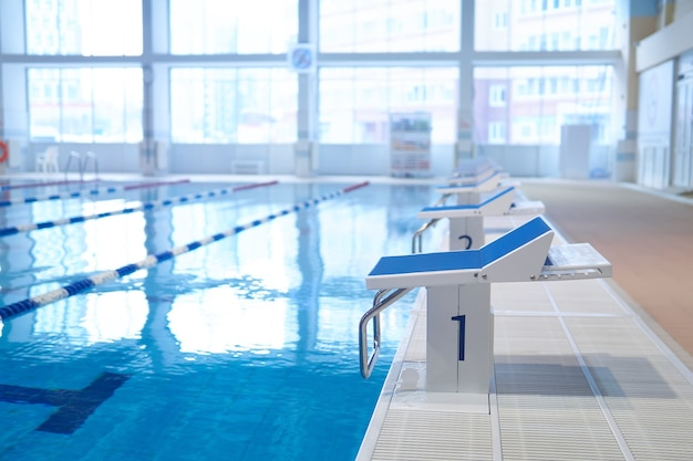 Частично размытый интерьер крытого спортивного бассейна с рядом трамплинов