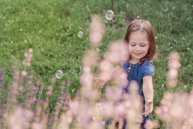 Partially blurred little girl 3-4 with dark hair in denim dress catches soap bubbles, on the lawn near flowers