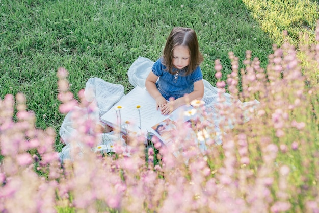 Partially blurred little girl 3-4 with dark hair in denim dress sits and reads book, on lawn near flowers