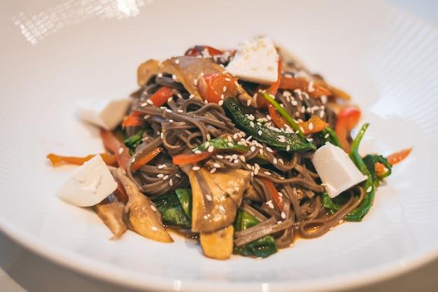 시금치, 굴 버섯, 토마토, 참깨, 두부를 곁들인 메밀 국수 부분적으로 흐린 접시. 비건 요리