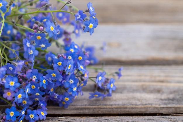 소박한 나무 표면에 부분적으로 흐릿한 부드러운 꽃. 오래 된 보드에 물망초의 꽃다발입니다. 공간을 복사합니다.