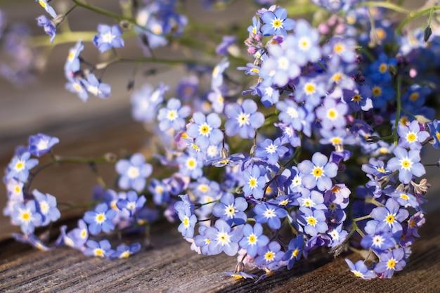 소박한 나무 표면에 부분적으로 흐릿한 부드러운 꽃. 소박한 오래된 보드에 물망초의 꽃다발.