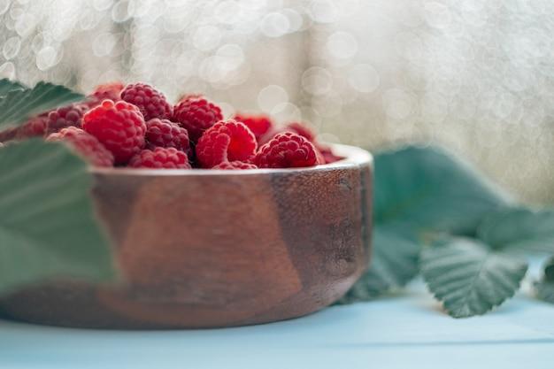 Частично размытая деревянная круглая миска, полная спелой красной сочной малины на белой деревянной поверхности на фоне боке с листьями малинового куста