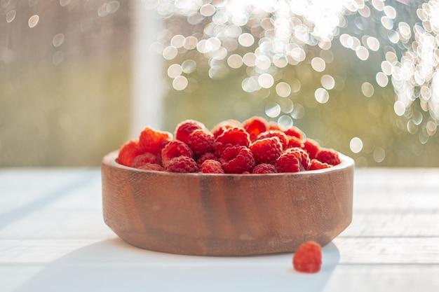 Частично размытая деревянная круглая миска, полная спелой красной сочной малины на белой деревянной поверхности, на фоне боке