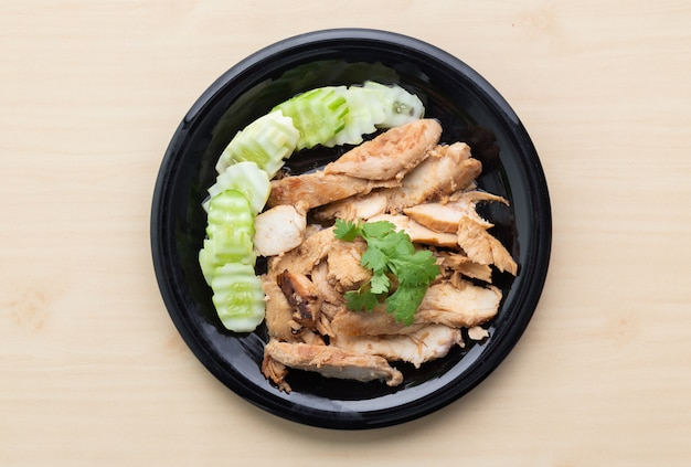 Partially sliced grilled chicken breast with cucumber in black plate on wooden table.
