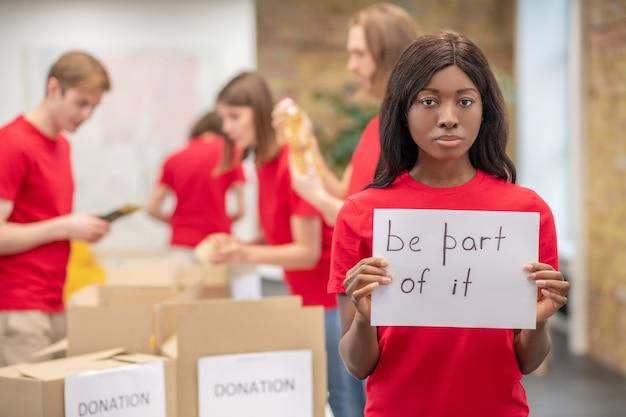 Участие, волонтерство. молодая целеустремленная американка в красной футболке-волонтере показывает плакат с лозунгом, чтобы помочь нуждающимся