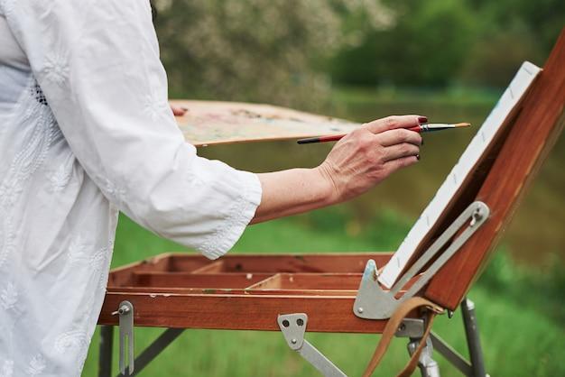 Vista delle particelle della donna adulta pittore che lavora sulla vernice all'esterno