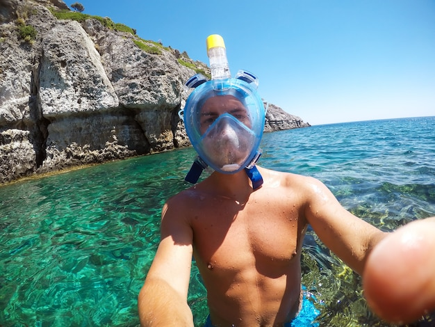 Partly blurred image because of drops of water. young male explorer in adventure ready for snorkeling. selfie shot at summer day at rock in the middle of the sea.