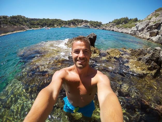 水滴により画像が部分的にぼやけています。シュノーケリングの準備ができて冒険の若い男性の探検家。 selfieは、夏の日に海の真ん中にある岩で撮影しました。