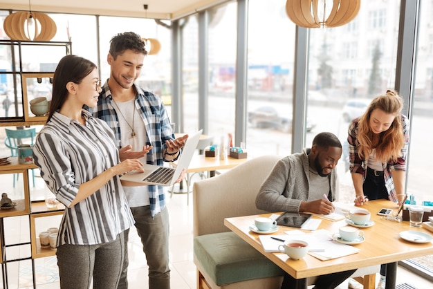パートナーの決定。かなり若い女性がノートパソコンを持って、重要なビジネス情報について話し合っている間、男性の同僚の近くに立っています。