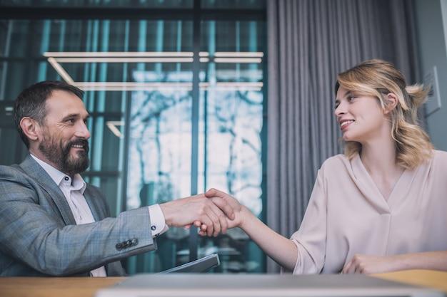 パートナー、ビジネス。笑顔のビジネス大人のひげを生やした男と金髪の若い女性がオフィスで同意して握手して座っている