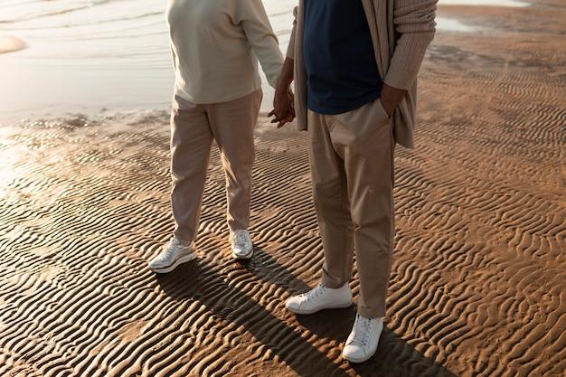 海辺で手をつないでいるパートナーがクローズアップ