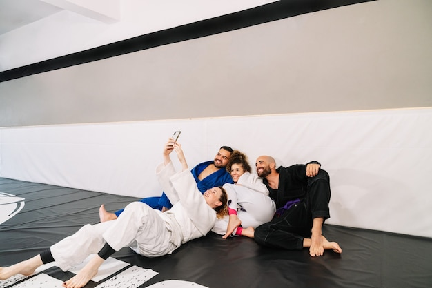 Partners of martial arts like judo using kimono sitting on the carpet of the floor and leaning on the wall of the gym, making a selfie with the mobile very happy