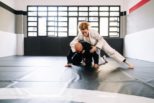 Partners in a martial arts training with kimonos practicing techniques on the gym mat all wearing face masks due to the covid 19