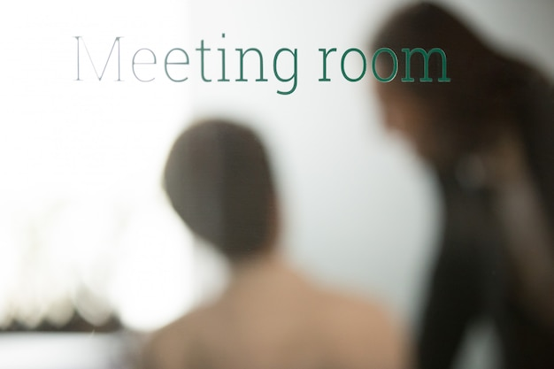 Partners negotiating behind closed glass door of meeting room