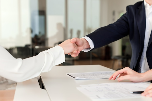Partners shaking hands and cooperating on a deal in the office