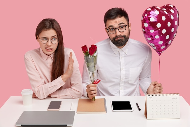 Partners at work sort out relationships. displeased woman refuses to recieve bouquet and valentine from male colleague, rejects courtship
