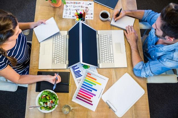 Партнеры, работающие на столе, используя ноутбук