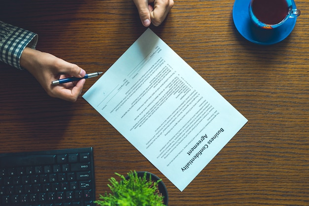 Partnership agreement business document signed by a person on the table in the  office