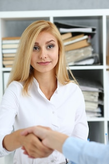 Partnership agreement closeup with woman in suit shake