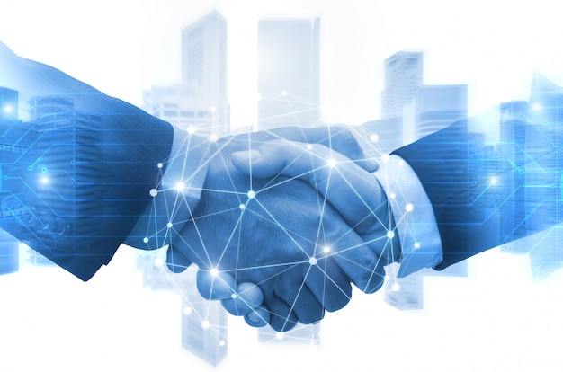Partnership - business man shaking hands with effect digital network link connection graphic diagram, digital global technology with cityscape background