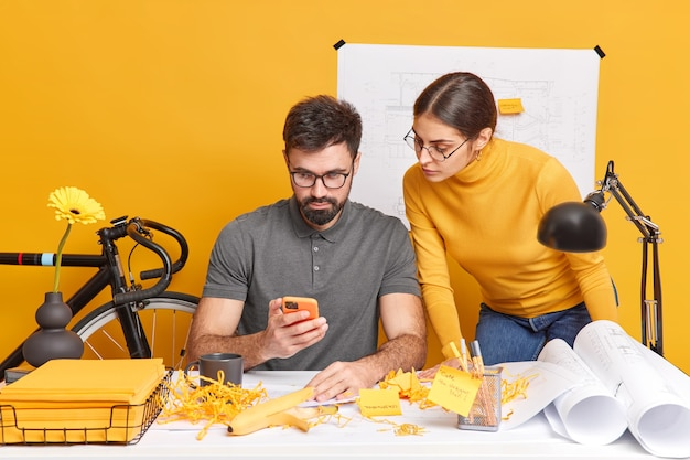Partnership and collaboration concept. busy woman and man designers or engineers work together think over blueprint pose at messy desktop concentrated at smartphone display discuss ideas for project