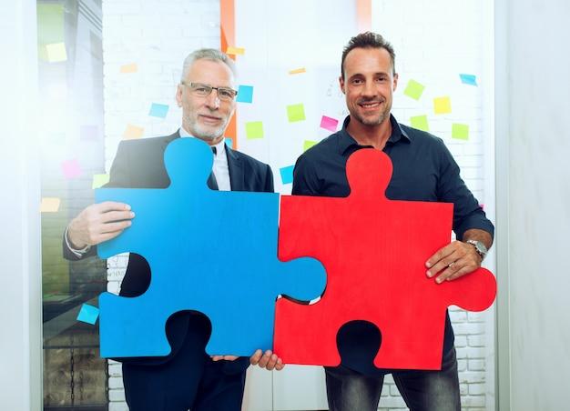 ビジネスマンのパートナーシップ。色のパズルのピースとの統合と起動の概念