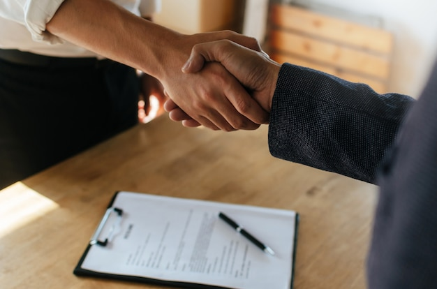 Partnership. two business people handshake after business signing contract in meeting room office