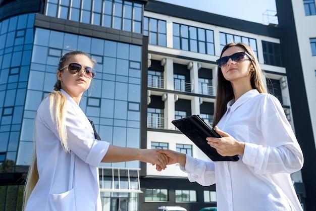 Партнерство. две молодые бизнес-леди пожимают друг другу руки возле офисного здания