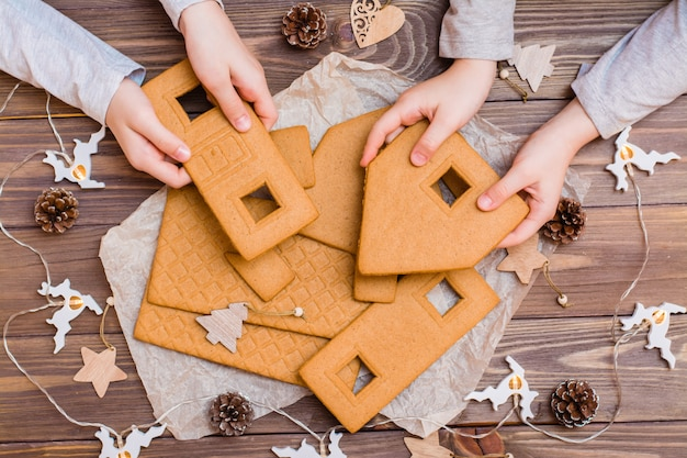 Parts of a disassembled christmas gingerbread house in children's hands and christmas decorations on a wooden background. christmas preparations